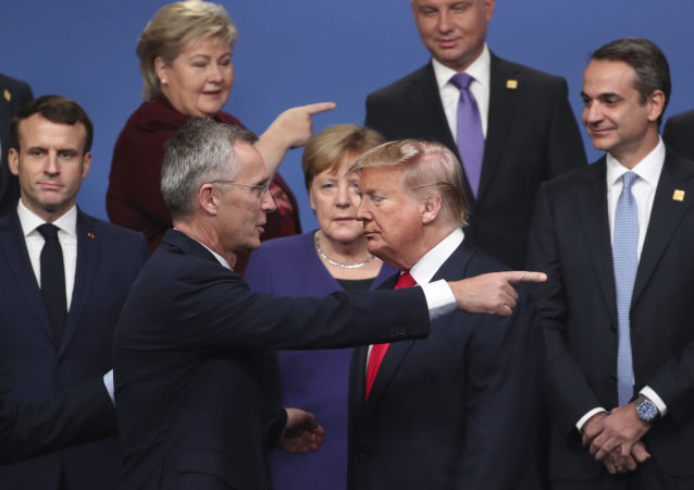 NATO Secretary General Jens Stoltenberg, center front left, speaks with U.S. President Donald Trump, center front right, after a group photo at a NATO leaders meeting at The Grove hotel and resort in Watford, Hertfordshire, England, Wednesday, Dec. 4, 2019.