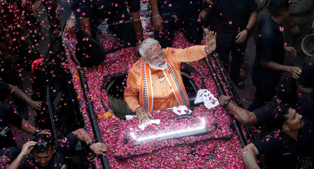India's Prime Minister Narendra Modi waves towards his supporters during a roadshow in Varanasi, India, April 25, 2019