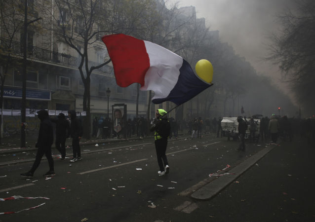 A man waves a French flag during a demonstration in Paris, Thursday, Dec. 5, 2019. Small groups of protesters are smashing store windows, setting fires and hurling flares in eastern Paris amid mass strikes over the government's retirement reform. (AP Photo/Rafael Yaghobzadeh)