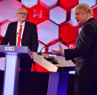 In this handout photograph taken and released by the British Broadcasting Corporation (BBC) on December 6, 2019, Britain's Prime Minister Boris Johnson (R) and Britain's main opposition Labour Party leader Jeremy Corbyn participate in the BBC Prime Ministerial leaders debate, at the studio in Maidstone, Kent.