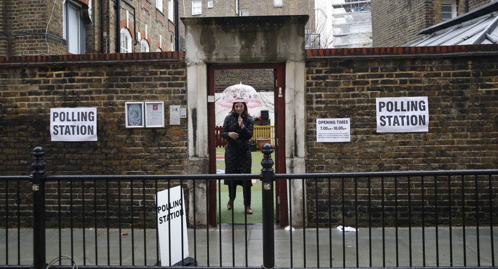 A woman leaves a polling station in London, Thursday, 12 December 2019