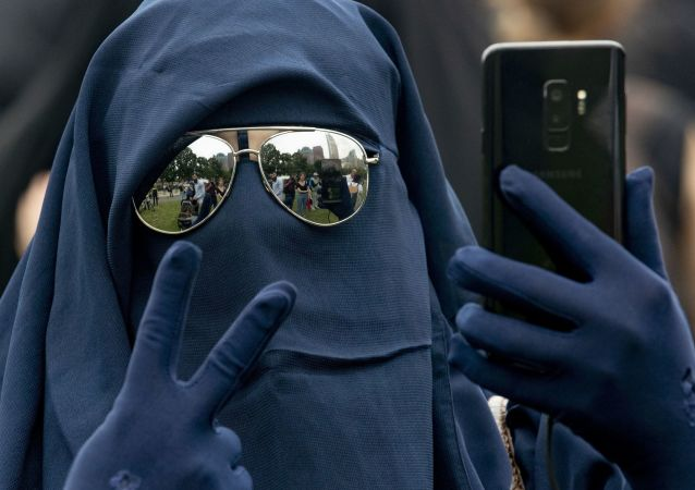 A woman wearing a niqab takes a selfie while flashing the victory sign as she takes part in a demonstration against a ban on face-covering veils in The Hague on 9 August 2019.