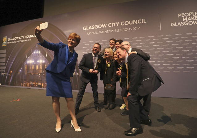 Scottish First Minister Nicola Sturgeon takes a photo with party members at the SEC Centre in Glasgow after the declaration in her constituency in the 2019 general election, Friday Dec. 13, 2019