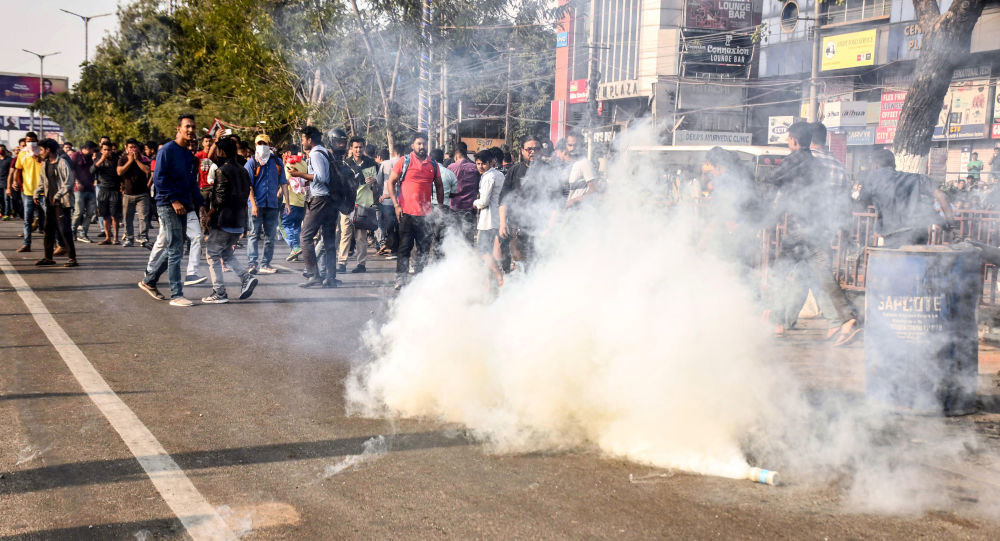 Police personnel fire tear gas to disperse the students protesting against the government's Citizenship Amendment Bill (CAB), during a demonstration in Guwahati on December 11, 2019