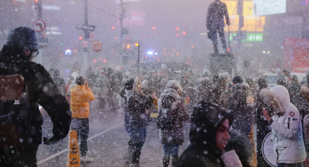 Pedestrians observe a snow squall in Times Square Wednesday, Dec. 18, 2019, in New York. (AP Photo/Frank Franklin II)