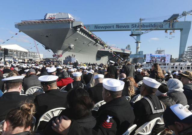 Spectators take their seats as they wait for ceremonies to begin for the christening of the nuclear aircraft carrier John F. Kennedy at Newport News Shipbuilding in Newport News, Va., Saturday, Dec. 7, 2019. (AP Photo/Steve Helber)