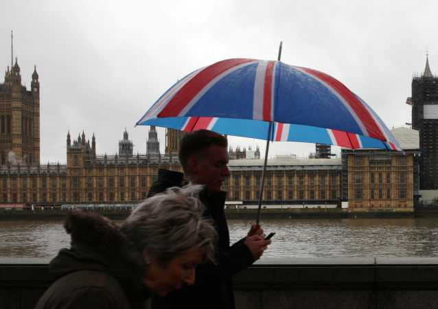 People walk over Westminster Bridge on a rainy day wiht the Houses of Parliament in the background in London, Britain, December 20, 2019. REUTERS/Tom Nicholson NO RESALES. NO ARCHIVES.