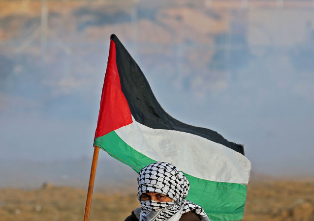 A Demonstrator holds Palestinian flag at the Israel-Gaza border fence during an anti-Israel protest, in the southern Gaza Strip December 6, 2019