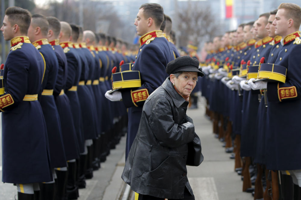 A woman walks by honor guard soldiers during a memorial religious service at the Heroes' cemetery, to honor those killed in the anti-communist  uprising, in Bucharest, Romania.