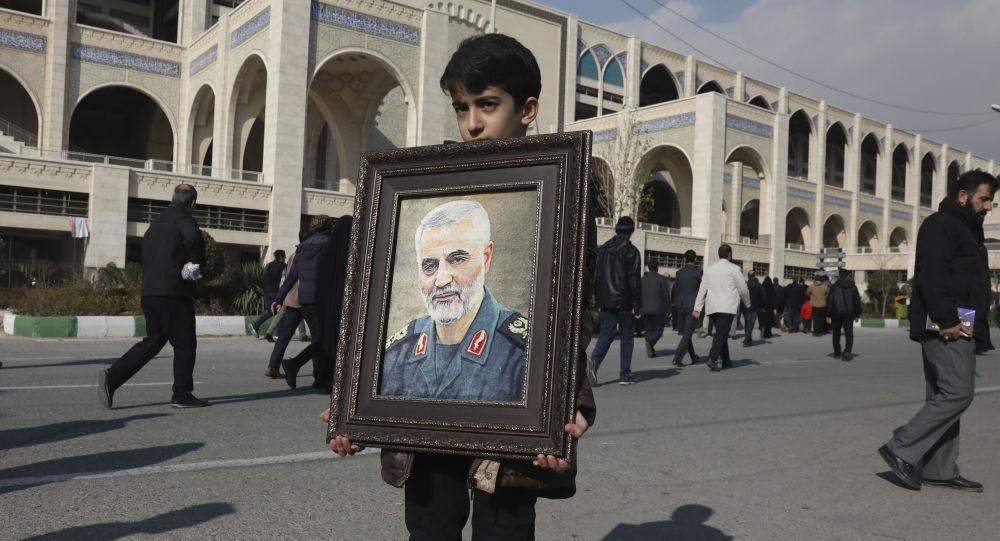 A boy carries a portrait of Iranian Revolutionary Guard Gen. Qassem Soleimani