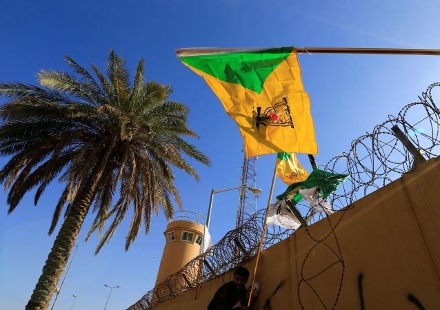 member of Hashd al-Shaabi (paramilitary forces) holds a flag of Kataib Hezbollah