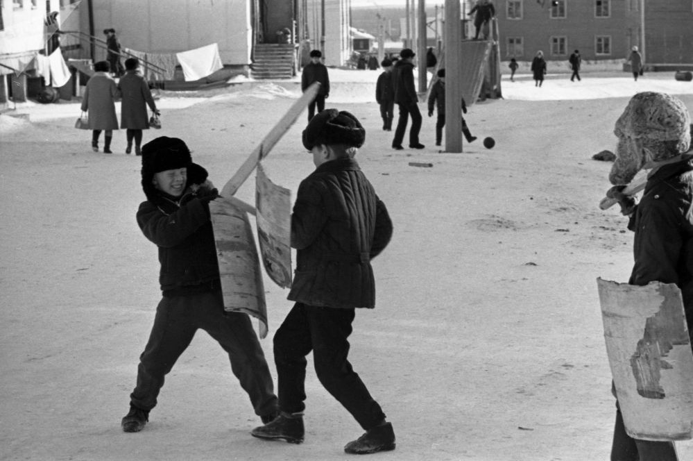 Boys are fighting using wooden swords and shields during a winter day in Yakutsk in 1973