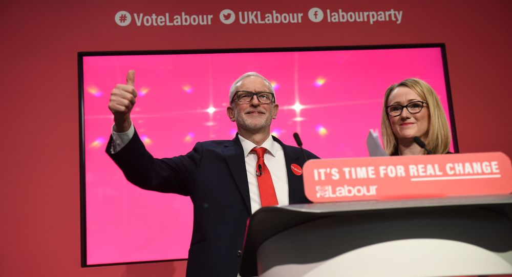 Britain's  Labour Party shadow Business Secretary Rebecca Long-Bailey (R) stands with Britain's opposition Labour Party leader Jeremy Corbyn during the launch of the Labour party election manifesto in Birmingham, northwest England on November 21, 2019.