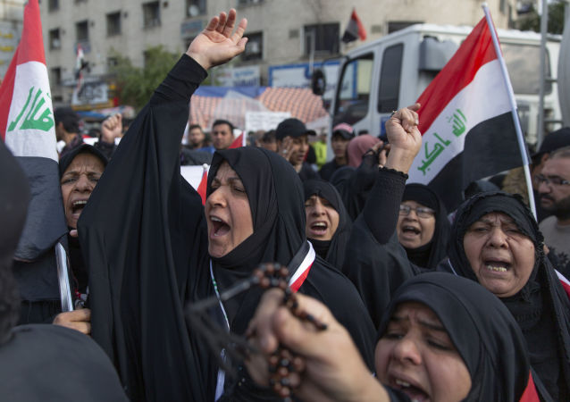 Anti government Iraqi women protesters chant anti Iran and anti U.S. slogans during the ongoing protests in Tahrir square, Baghdad, Iraq, Friday, Jan. 10, 2020.