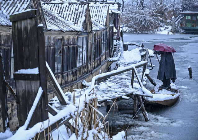 A man removes snow from a boat on the banks of the the Dal Lake during a snowfall in Srinagar on January 13, 2020