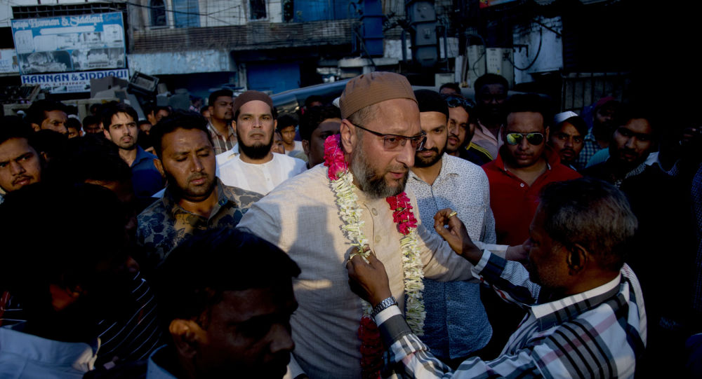 An Indian supporter present a floral garland to All India Majlis-e-Ittehadul Muslimeen (AIMIM) President Asaduddin Owaisi, center, during an election campaign in Hyderabad, India, Tuesday, March 26, 2019