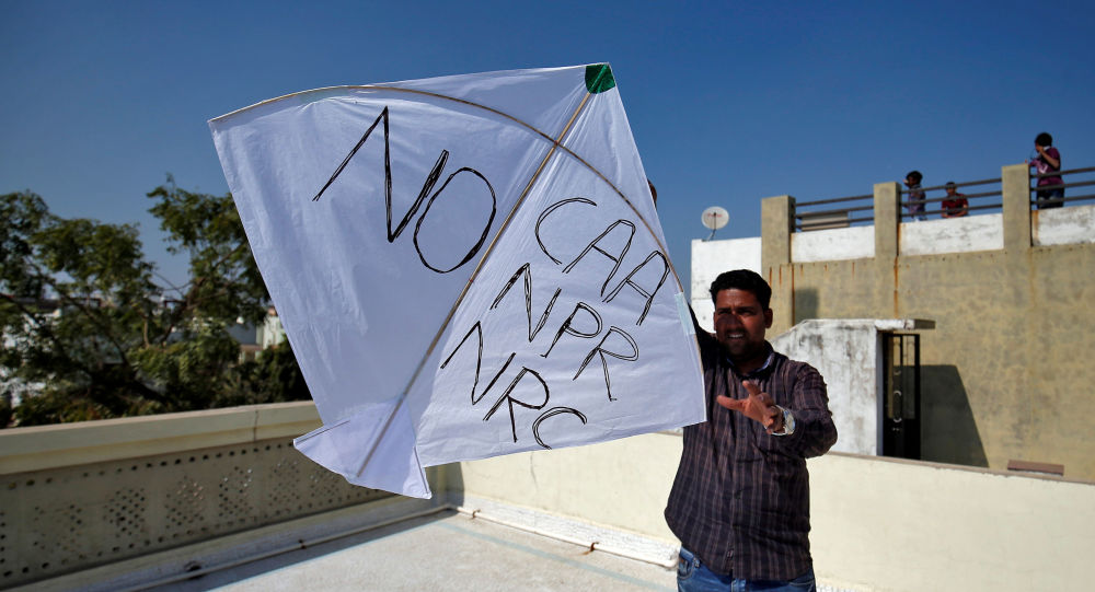 A man tries to fly a kite with a message, as part of a protest against a new citizenship law, on the occasion of kite flying festival, locally known as Uttarayan, in Ahmedabad, India, January 14, 2020