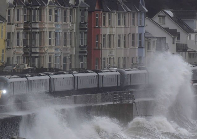 Large waves hit the sea wall with Storm Brendan bringing high winds and heavy rain, as a train passes through Dawlish, southwest Britain, January 14, 2020.