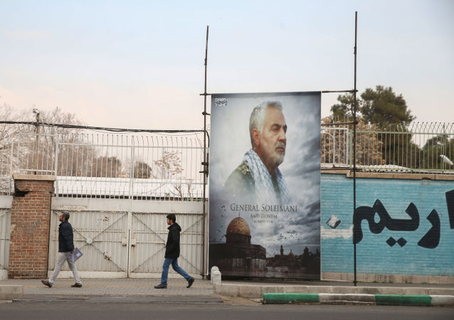 People walk past a picture of Iranian Major-General Qassem Soleimani, head of the elite Quds Force, who was killed in an air strike at Baghdad airport, as it is seen in front of the former U.S. Embassy's building in Tehran, Iran, January 21, 2020