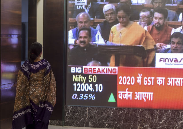 A woman stands as she watches a screen displaying a television channel live broadcast of India's Finance Minister Nirmala Sitharaman (C on screen) presenting the 2020 union budget, at the Bombay Stock Market (BSE) in Mumbai on February 1, 2020.