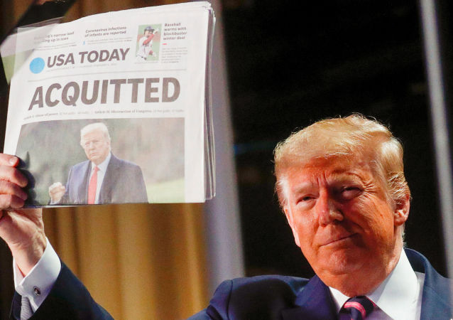 U.S. President Donald Trump holds up a copy of USA Today's front page showing news of his acquitttal in his Senate impeachment trial, as he arrives to address the National Prayer Breakfast in Washington, U.S., 6 February, 2020.