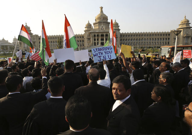 Indian lawyers hold national flags and form a human chain as they protest outside the Vidhan Soudha, Karnataka state's seat of power, against a new citizenship law that opponents say threatens India's secular identity, in Bangalore, India, Thursday, Jan. 9, 2020