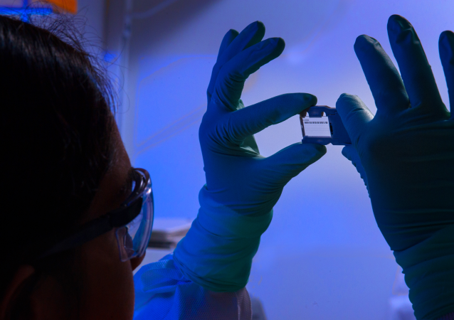 This photograph depicted an Enteric Diseases Laboratory Branch (EDLB) public health scientist, holding up a glass slide used for a run on a sequencing machine.