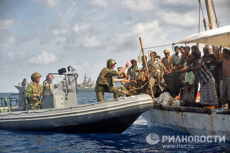 The Pyotr Veliky cruiser inspects a fishing boat