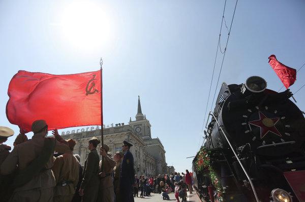 Молодые люди в военной форме времен Великой Отечественной войны стоят у ретро-поезда Победа