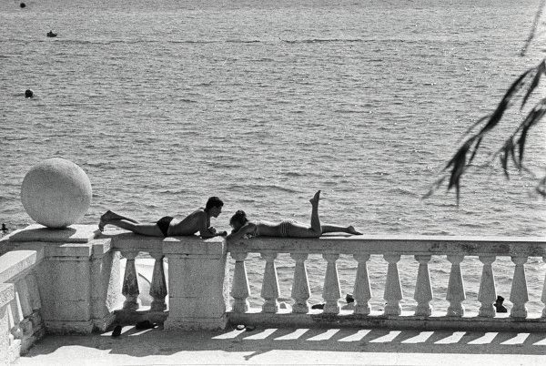 Отдыхающие загорают на ограде набережной в Сочи