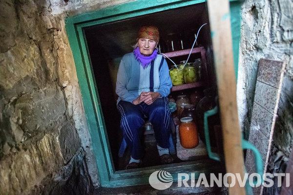 Жительница поселка Семеновка в погребе, в котором она пережидает артиллерийские обстрелы.