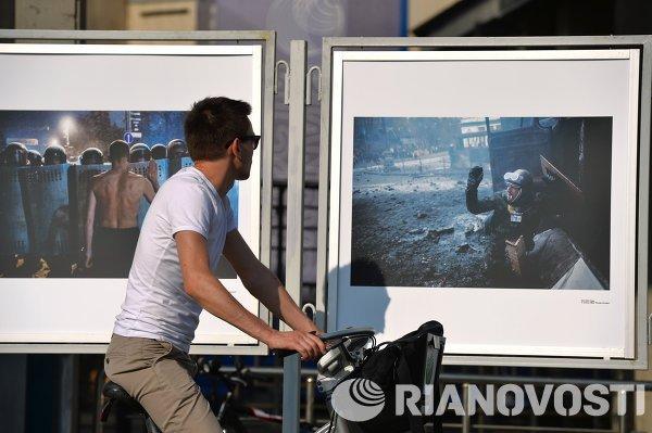 Мужчина смотрит на работы фотокорреспондента Андрея Cтенина
