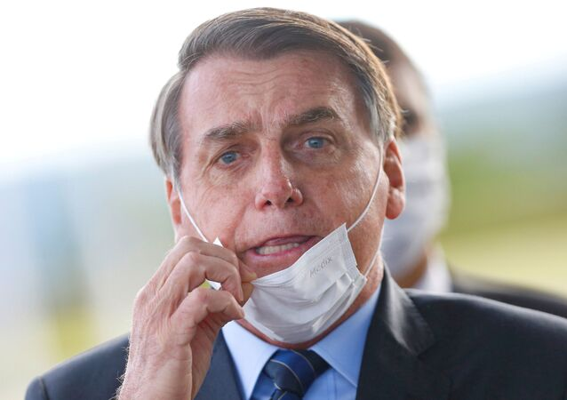 Brazil's President Jair Bolsonaro adjusts his mask as he leaves Alvorada Palace, amid the coronavirus disease (COVID-19) outbreak in Brasilia, Brazil May 13, 2020