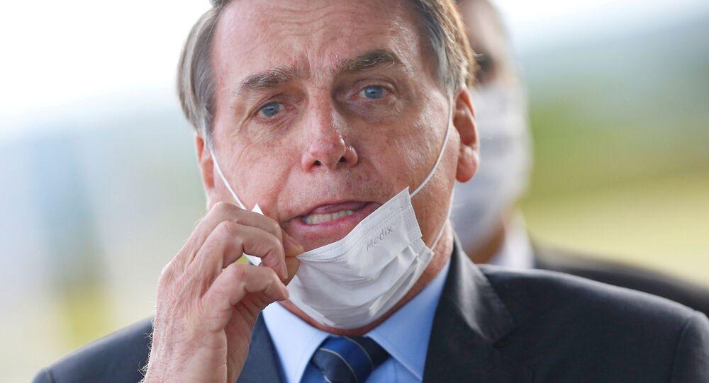 Brazil's President Jair Bolsonaro adjusts his mask as he leaves Alvorada Palace, amid the coronavirus disease (COVID-19) outbreak in Brasilia, Brazil May 13, 2020