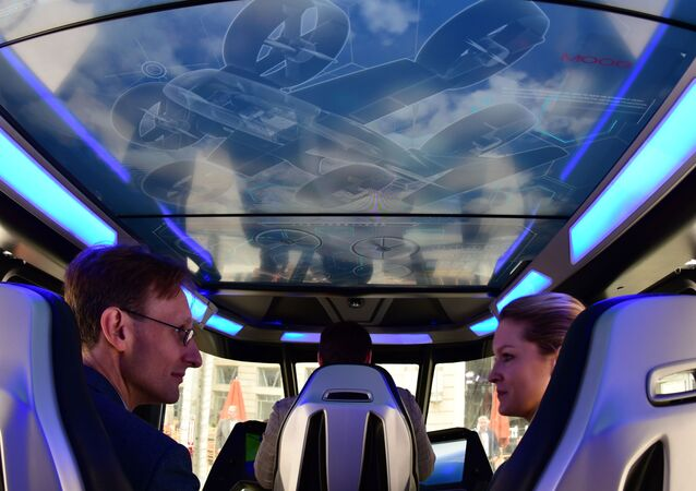 Visitors sit inside the Bell Nexus concept vehicle at the Uber Elevate Summit June 12, 2019 in Washington, DC, one of the vertical takeoff and landing (VTOL) vehicles or flying cars that will be part of Uber's fleet for aerial ride sharing.