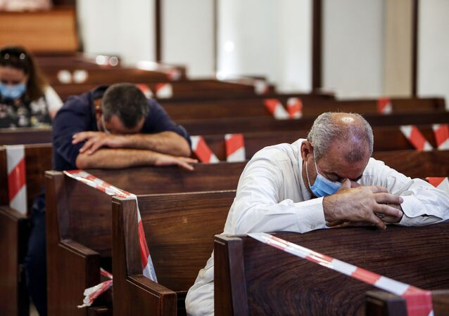 Mask-clad worshippers pray while seated in distanced pews during a service at the National Evangelical Church in Kuwait City on July 9, 2020 for the first time since the lifting of a lockdown due to the COVID-19 coronavirus pandemic.