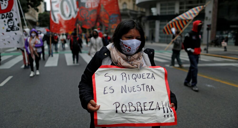A demonstrator holds a placard that reads their richness is our poverty, during a protest to demand resources for the vulnerable, amid the coronavirus disease (COVID-19) lockdown, in Buenos Aires, Argentina May 21, 2020.