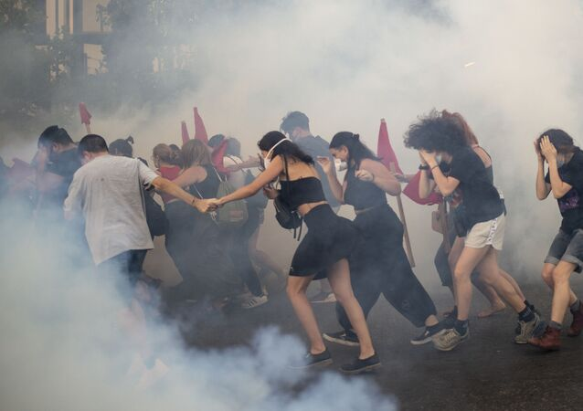 Protesters run amid tear-gas smoke outside the Greek parliament  in Athens
