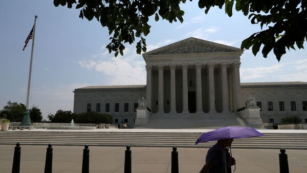 A pedestrian holding an umbrella walks along First Street, as a series of rulings are issued at the United States Supreme Court in Washington, U.S., July 6, 2020 - Sputnik International