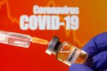 A small bottle labeled with a Vaccine sticker is held near a medical syringe in front of displayed Coronavirus COVID-19 words in this illustration taken April 10, 2020.
