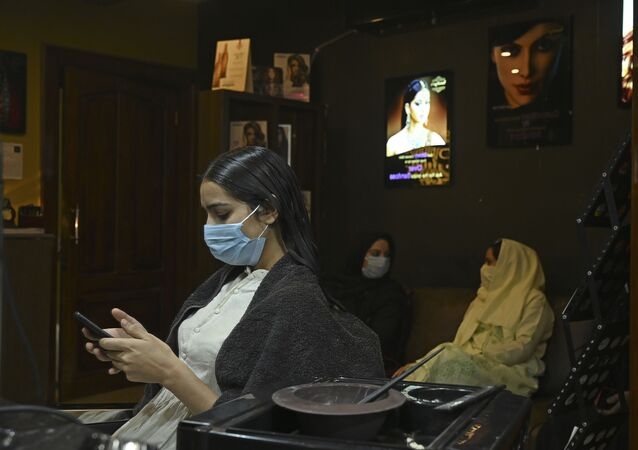 A customer wearing a facemask checks a mobile phone at a hair salon, after the government eased a nationwide lockdown as a preventive measure against the COVID-19 coronavirus, in Srinagar on June 15, 2020