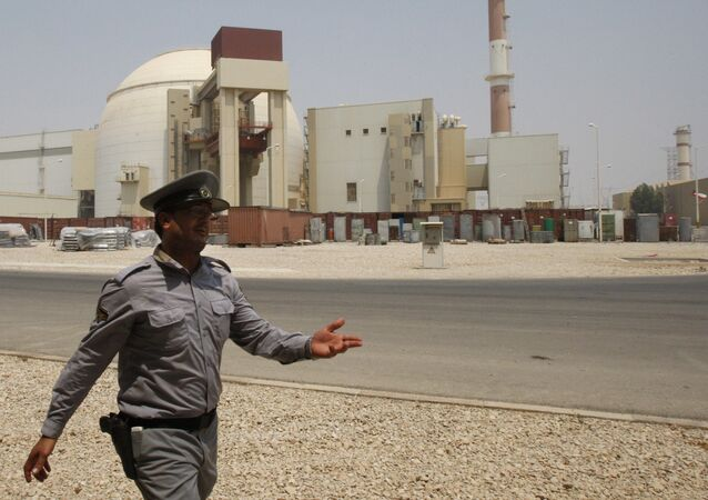 An Iranian security directs media at the Bushehr nuclear power plant, with the reactor building seen in the background, just outside the southern city of Bushehr, Iran, Saturday, Aug. 21, 2010