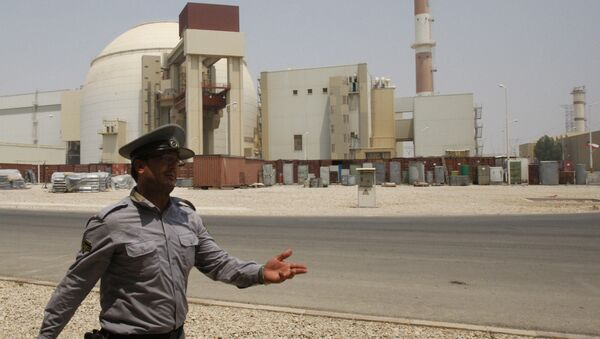 An Iranian security directs media at the Bushehr nuclear power plant, with the reactor building seen in the background, just outside the southern city of Bushehr, Iran, Saturday, Aug. 21, 2010 - Sputnik International