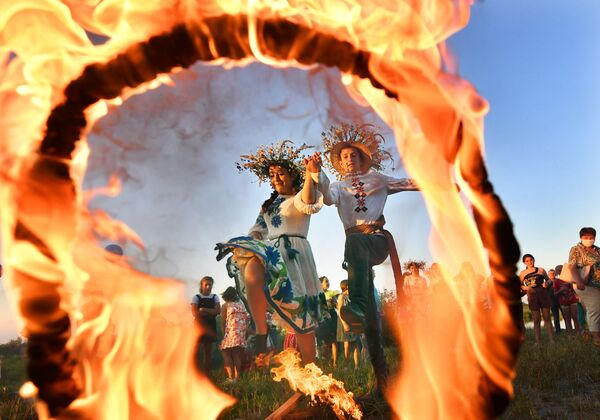 A girl and a young man jump over the fire during the festival of Ivan Kupala on the shore of the Gulf of Pripyat in the ancient Belarusian city of Turov. - Sputnik International