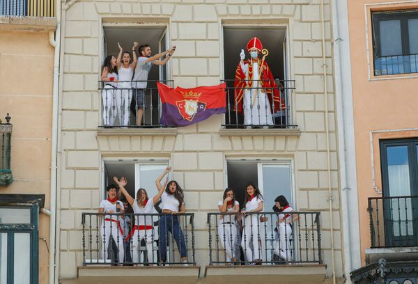 A reveller dressed up as Saint Fermin waves from a balcony in front of the town hall where the firing of chupinazo, which opens the San Fermin festival that was cancelled due to the coronavirus (COVID-19) outbreak, should have taken place, in Pamplona, Spain, 6 July 2020. - Sputnik International