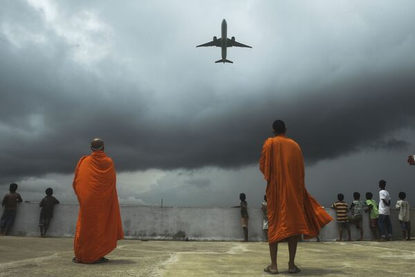 Buddhists monks and children look out from the rooftop at a Buddhist mission hostel and school for underprivileged children as an international passenger flight takes off at the Netaji Subhash Chandra Bose International Airport after the authorities eased restrictions imposed as a preventive measure against the spread of  COVID-19, in Kolkata on 5 July 2020.  - Sputnik International