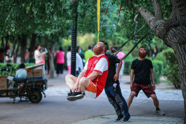 This photo taken on 5 July 2020, shows a man doing exercises as he hangs on a tree in Shenyang in the northeastern Chinese province of Liaoning. - Sputnik International