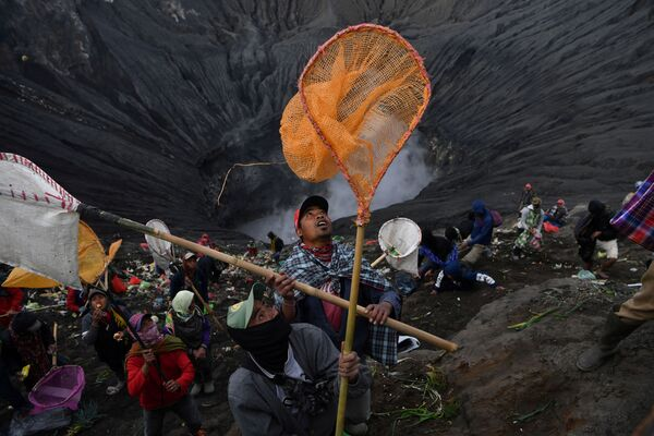 Villagers carry their nets in an attempt to catch coins thrown as offerings by Hindu worshippers into the crater during the Kasada ceremony at Mount Bromo in Probolinggo, East Java Province, Indonesia 7 July 2020. - Sputnik International