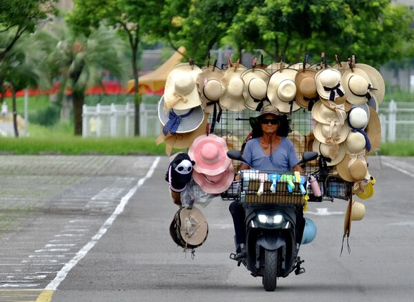 Wang Shang-chi, 75, a mobile hat vender, rides his bike in a parking lot next to the Taipei City Zoo on 9 July 2020. - Sputnik International