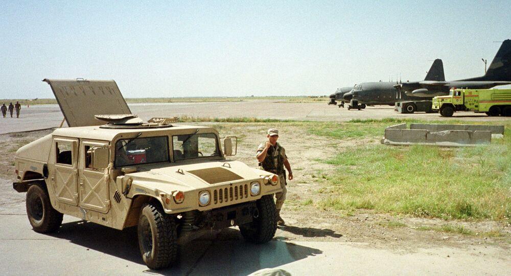 US Army soldier walks past a Humvee at the Karshi-Khanabad air base in Uzbekistan, 28 May 2002